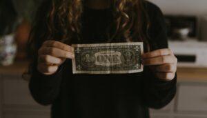 woman holding one dollar bill