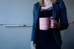 woman in grey blazer holding pink mug with do it anyway written on it