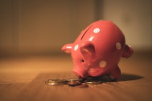pink piggy bank with money next to it