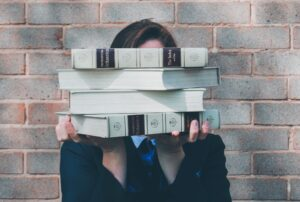 woman holding pile of books obscuring face