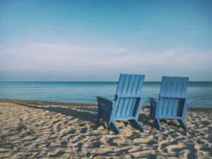 two blue beach chairs sitting on the beach facing the ocean